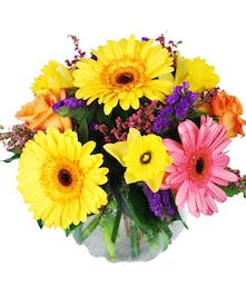 Bright yellow, pink and purple flowers in a glass bowl vase.