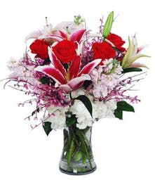 Stock, roses, stargazer lilies, hydrangea and ginestra flowers in a clear glass vase.