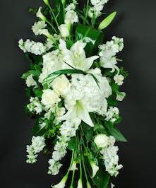 All-white sympathy spray of calla lilies, casablanca lilies, stock and hydrangea.