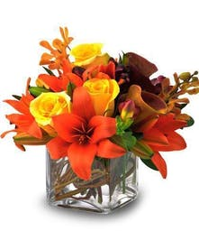 Lilies, roses and orchids in a clear glass cube vase.
