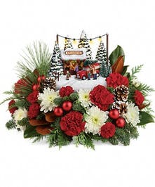 Red carnations, red miniature carnations, magnolia leaves, flat cedar, noble fir and white pine surrounding a Thomas Kinkade keepsake.