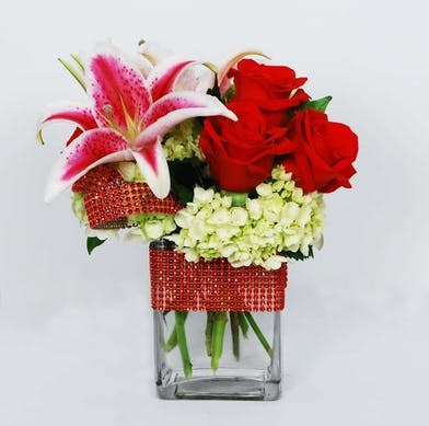 Roses, hydrangea and stargazer lilies in a clear glass vase tied with red ribbon.