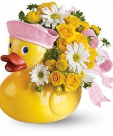 Large vase that looks like a rubber duck holding white and yellow flowers with a pink ribbon.