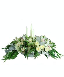 Elegant holiday centerpiece of white flowers, ribbon, candles and greenery.