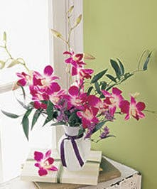 Dendrobium orchids, caspia, and Italian ruscus in a white glass vase.