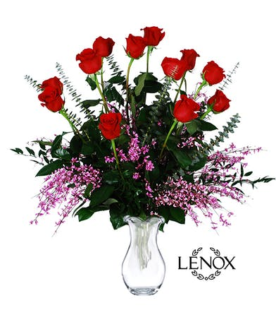 One dozen long stemmed red roses and greenery in a Lenox crystal vase.