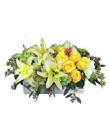 Centrpiece with bright yellow, green and white flowers and greenery