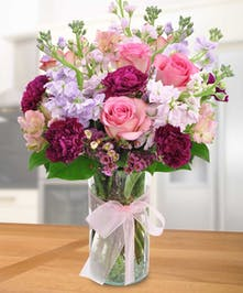 Pink roses, lavender stock and carnations in a clear glass vase tied with pink ribbon.