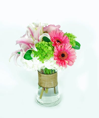 Pink oriental lilies, green hydrangea, pink gerbera daisies, and roses in a clear glass vase.
