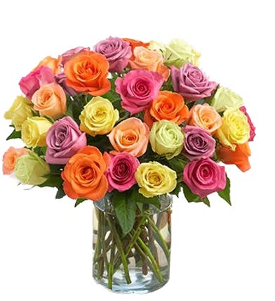 Roses in shades or orange, yellow, pink and purple in a clear glass vase.