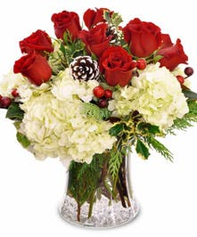 Holiday arrangement of white hydrangea, red roses, berries, pine cones and more.