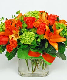 Lilies, roses and hydrangeas with greenery in a rectangle vase.