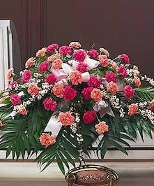 Casket spray of dark and light pink carnations and assorted greenery.