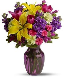 Colorful yellow, raspberry, purple and green flowers in a purple glass vase.