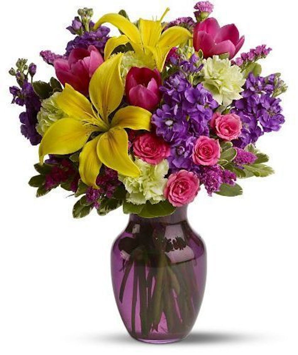 Colorful yellow, raspberry, purple and green s in a purple glass vase.