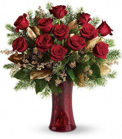 One dozen Christmas roses arranged with holiday accents in a tall red vase.