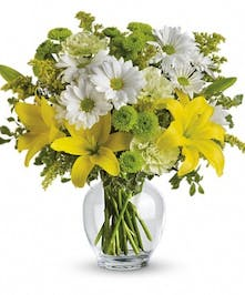 Yellow and green flowers in a glass vase.