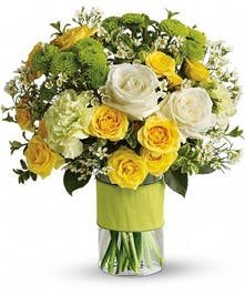 White and yellow roses and other flowers in a glass cylinder vase.