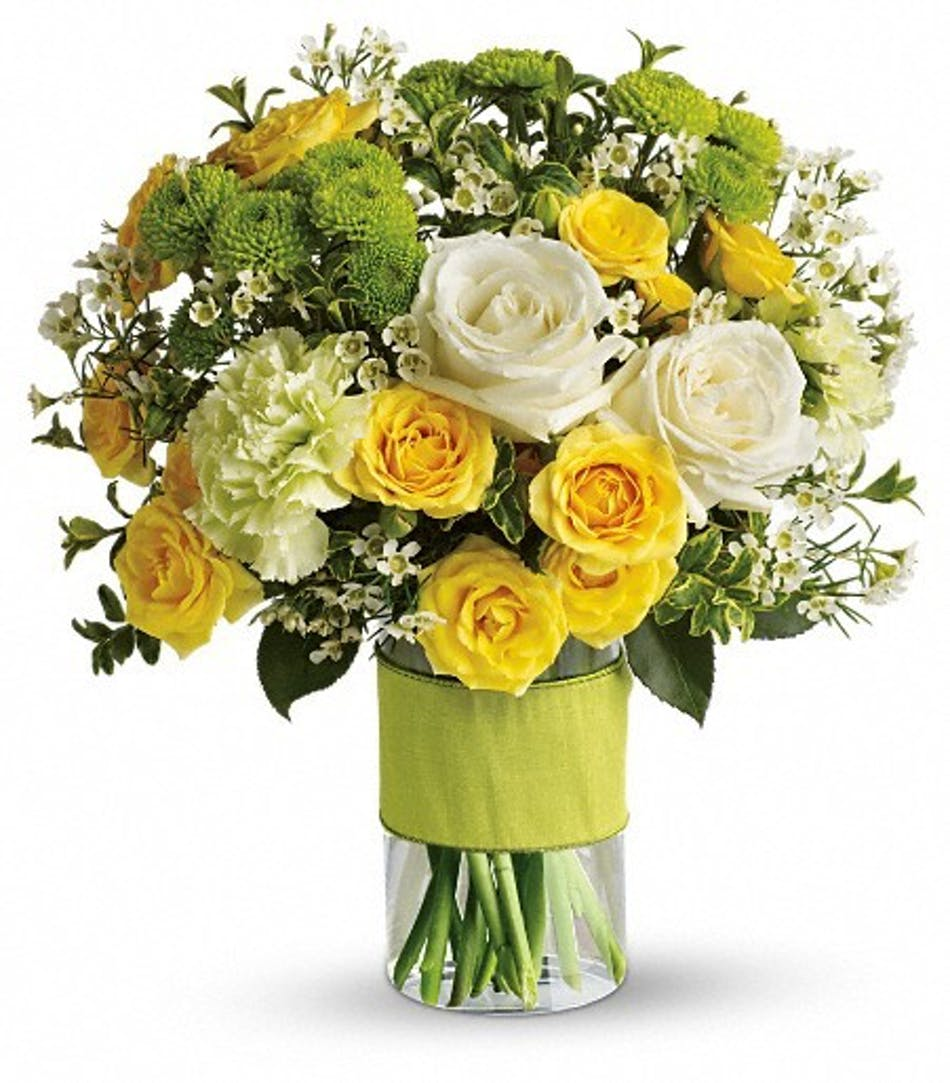 White and yellow roses and other s in a glass cylinder vase.