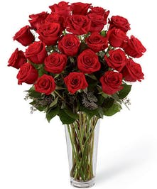 Two dozen (24) long stem red roses with baby's breath and greenery in a clear glass vase.