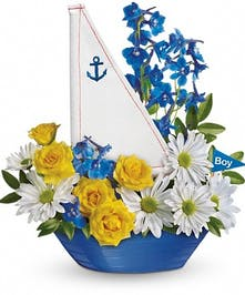 Yellow spray roses, blue delphinium, and white daisy spray chrysanthemums in a charming sailboat container.