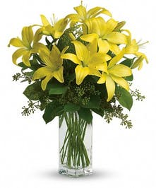 Bright yellow lilies and greenery in a clear glass vase.