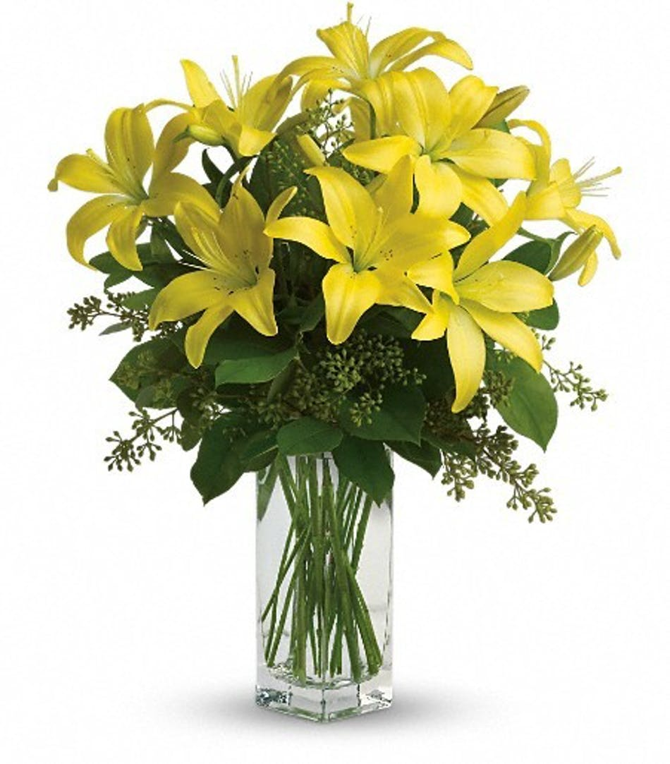 Yellow lily flower arrangement als florist hollywood bright yellow lilies and greenery in a clear glass vase izmirmasajfo