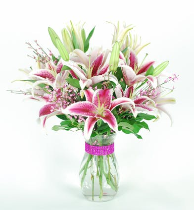 Stargazer lilies in a clear glass vase.