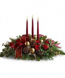 Christmas centerpiece of red flowers, greenery, pine cones, ornaments, ribbon and candles.