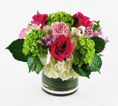 Pink roses, lime green hydrangea, white hydrangea, calla lilies and accent flowers in a leaf lined vase.
