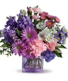 Purple and pink flowers in a purple glass cube vase.