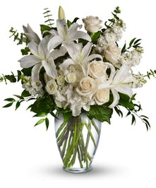 White lilies and roses with greenery in a clear glass vase.
