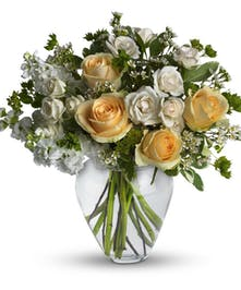 Peach roses, creme spray roses, white stock and waxflower in a clear glass vase.