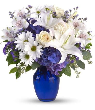 White roses, lilies, blue hydrangea and other flowers in a blue glass vase.