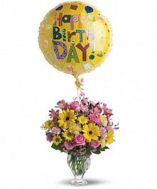 Pink and yellow flowers in a glass vase with a yellow Happy Birthday balloon.