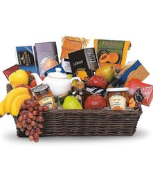 Wicker basket filled with fresh fruit, biscuits, chocolate and tea with a charming teapot.