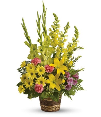 Basket of yellow asiatic lilies, snapdragons, daisy spray chrysanthemums, green gladioli and more.