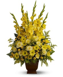 Mix of yellow flowers in a bright sympathy tribute.