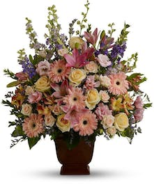 Sympathy arrangement of pastel blossoms in an urn.