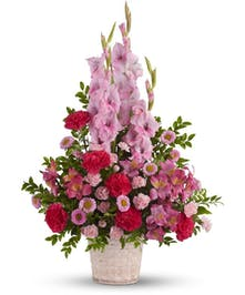 Pink gladioli, alstroemeria and carnations in a white basket planter.