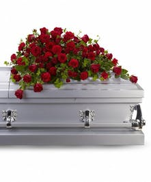 All-red casket spray of roses and carnations accented with ivy.