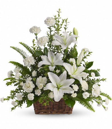 White lilies and greenery in a large sympathy basket for a funeral or service.