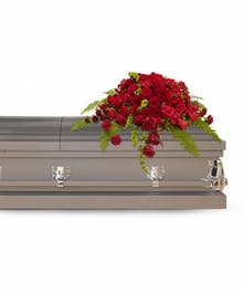 Casket spray of red roses, gerberas, gladioli and carnations with green bells of Ireland.
