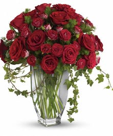 Brilliant red roses and spray roses along with vibrant fern and ivy are perfectly arranged in an exclusive Jewel vase.