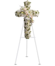 Floral cross of white and creme flowers.