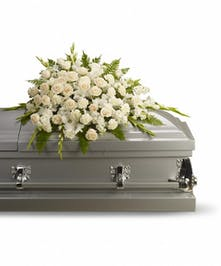 All-white casket spray of creme roses, white gladioli, stock and carnations with graceful ferns.