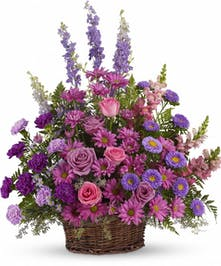 Pink, purple and lavender flowers in a sympathy funeral wicker basket.