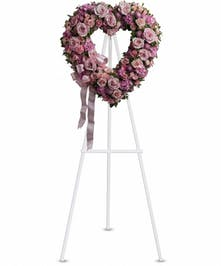 Light pink roses, hydrangea and mini carnations with lavender mums in a heart-shaped sympathy arrangement with coordinating ribbon.