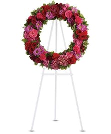 Hot pink an lavender flowers arranged in a sympathy wreath on an easel.