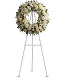 Sympathy wreath of all-white flowers delivered on an easel.